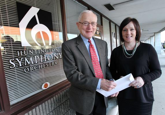 Lori Wolfe/The Herald-Dispatch | Huntington Symphony Orchestra Board of Trustees President Dr. Maurice Mufson gives free tickets for Saturday's performance to Alissa Stewart, executive director of Goodwill Industries of KYOWVA, on Tuesday, Dec. 16, 2014, in Huntington. The tickets will be distributed to youth at the J.W. Scott Community Center, operated by Goodwill Industries of KYOWVA, and the A.D. Lewis Center.